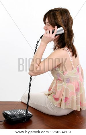 Beautiful young Hispanic woman speaking on telelphone.  Sitting on desk, wearing casual clothing.  Shot in studio over white.