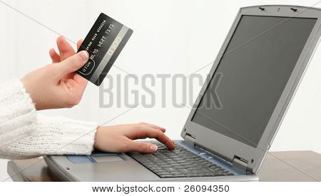 Woman's hand at table with Gold Card and Laptop computer.  Shopping or Paying Bills. Shot in studio.