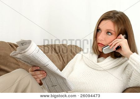 Beautiful young woman wearing sweater and glasses. Sitting on couch with cup of coffee reading newspaper.