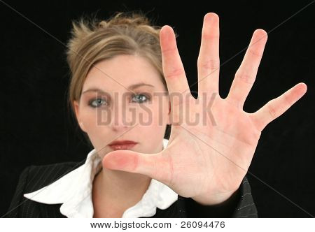 Beautiful Business Woman with Hand Palm Out in Front of Her. Shot in studio over black. Focus on hand.