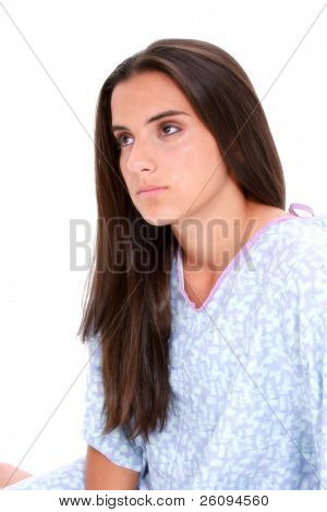 Beautiful dark haired teen girl in hospital gown crying. Eyes red with tears falling down cheeks.