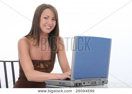 Beautiful young woman in casual clothes working on laptop computer.  Fantastic teeth and beautiful complextion.  Sitting at tile top bistro table over white background.