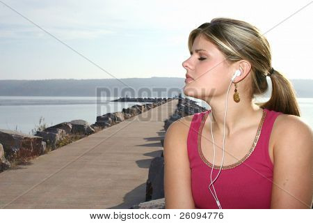 Young woman listening to music outside by the lake.
