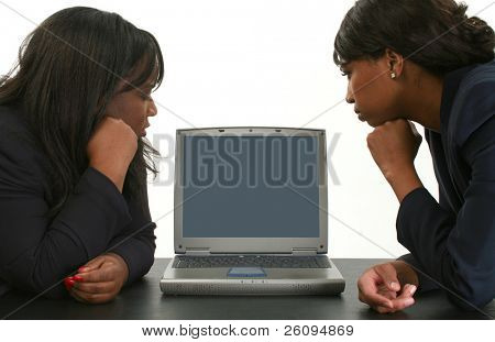 Two beautiful business woman (29 and 33) looking concerned towards laptop screen.  Add text.