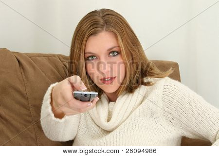 Woman aiming remote control towards camera.  Sitting on couch.  Wearing cream sweater.