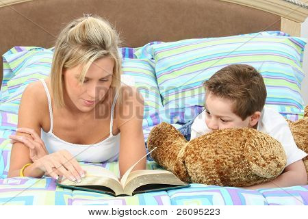Mother and son in pajamas reading book in bed together.