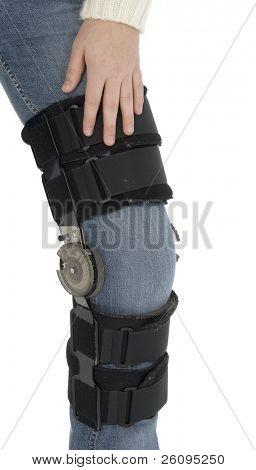 Woman's leg wearing knee brace over jeans.  Shot in studio over white.