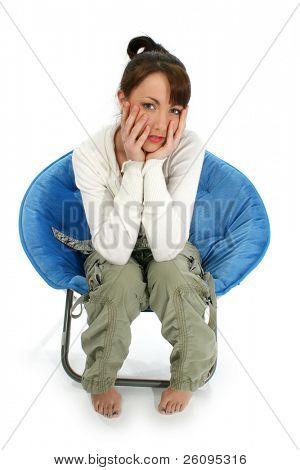 Joven descalza en la silla con las manos en la cara.  Disparó en estudio sobre el blanco.