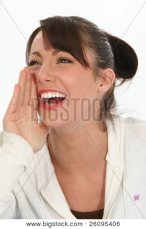Beautiful young woman with hand at mouth, smiling and calling out.
