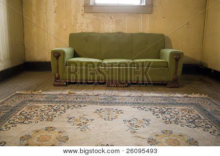 Vista del apartamento grungy habitación con sofá desagradable, alfombra y paredes agrietadas.  Telas de araña en la ventana.