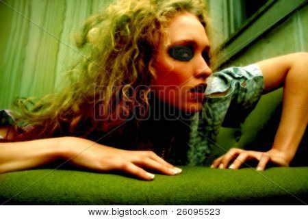 Focus on eye.  Young woman in hospital gown in a grungy room.  Goth make-up and dirty hair.