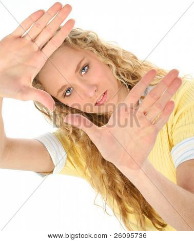 Beautiful blonde teen looking through raised hands. Palms out. Shot in studio.