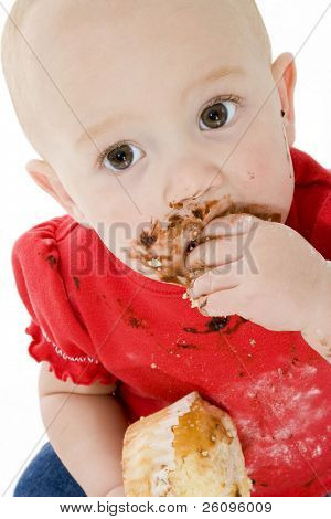 Baby with a face full of chocolate icing and cake crumbs.