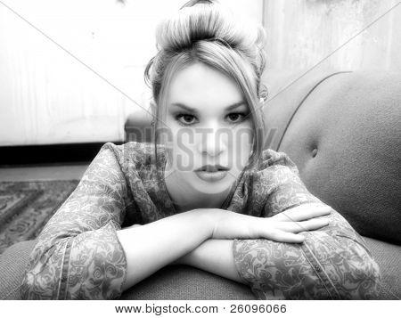 Mulher bonita de hispânicos deitado no sofá em apartamento sujo.  Preto e branco.