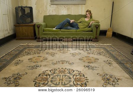 Beautiful Hispanic woman sitting in impoverished apartment.