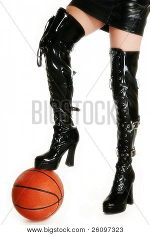 Female legs in thigh high vinyl boots with basketball over white.