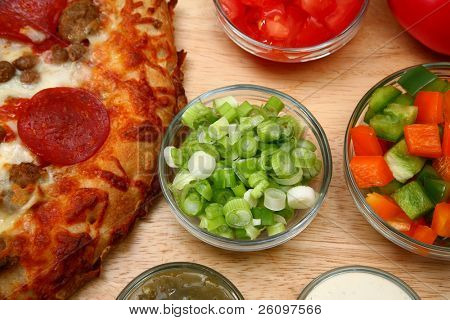 Bowl of chopped green onions surounded by pizza and toppings.
