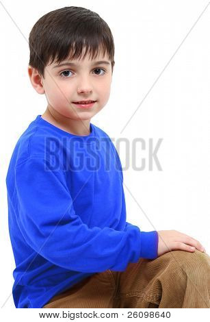 Adorable six year old boy casual portrait over white.  Blue shirt and tan pants.