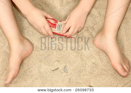 Young child's hands and feet in sand playing with car and money.