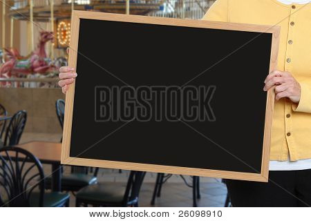 Woman holding blank chalkboard in front of carousel restaurant area.