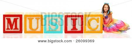 Colorful alphabet blocks. spelling the word music with beautiful six year old girl.