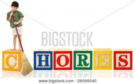 Unhappy attractive 7 year old french american boy doing chores with broom over white background.  Alphabet blocks spell Chores.