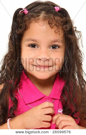 Adorable 3 year old mixed race girl buttoning her shirt over white background.