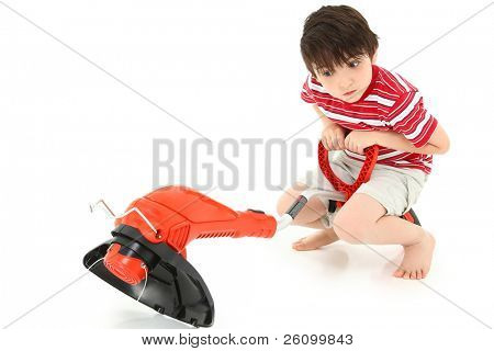 Adorable seven year old french american boy with weed whacker over white background.