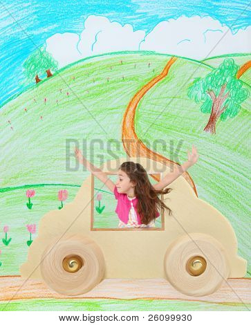 Adorable 6 year old french american girl in a toy wooden car traveling down an imaginary country road.