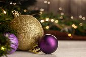 Christmas Toy Golden Ball Next To A Purple Ball With A Pattern On A Light Table In The Background A  poster