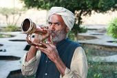 GWALIOR, INDIA -17 FEBRUARY: Old Indian man with turban blowing a trumpet in front of Gwalior Fort c