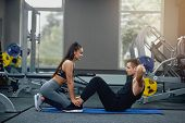 Handsome Man Doing Abdominal Crunches Press Exercise On Mat With Sports Female Personal Trainer In G poster