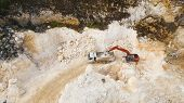 Excavator Loads The Truck In A Limestone Quarry. Aerial View Wheel Loader Excavator Machine Loading  poster