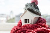 House In Winter - Heating System Concept And Cold Snowy Weather With Model Of A House Wearing A Knit poster