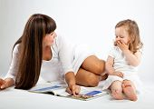 Mother little daughter reading book. Gray background