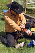 picture of bucking bronco  - rodeo cowboy preparing his glove and equipement for bull riding competition - JPG