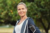 Portrait of a smiling healthy woman with earphones standing in park after running. Proud mature woma poster
