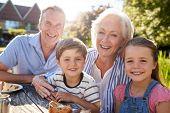 Portrait Of Grandparents With Grandchildren Enjoying Outdoor Summer Snack At Cafe poster