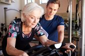 Senior Woman Exercising On Cycling Machine Being Encouraged By Male Personal Trainer In Gym poster