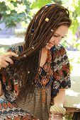 Cute smiling hippie indie style woman with dreadlocks, dressed in boho style ornamental dress posing poster