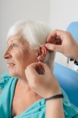 Cropped Doctors Hand Applying Hearing Aid For An Aged Woman poster