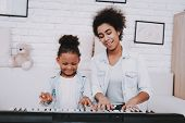 Black Girl And Mother Teach Young Girl Play On Piano. Child And Mother Play On Piano Together. Happi poster