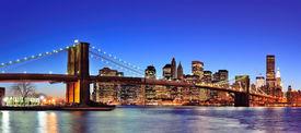 image of brooklyn bridge  - Brooklyn bridge with New York City Manhattan downtown skyline panorama at dusk illuminated over East River with blue clear sky - JPG
