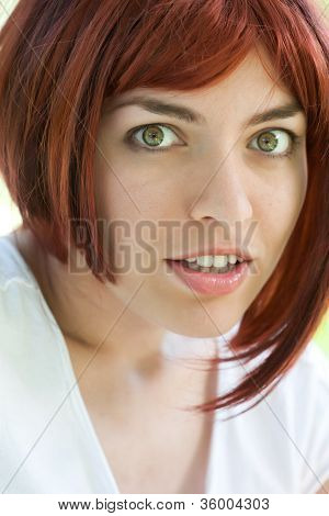 Portrait of the beautiful girl with red hair