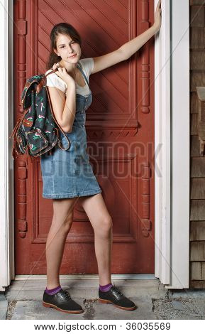 Smiling Teenage Girl With Backpack Leans Against Old Red Door.