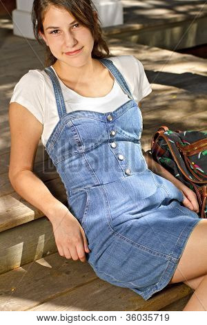 Smiling Teenage Girl In Denim Dress With Backpack Beside Her.