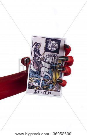 Devil's hand holding a tarot card