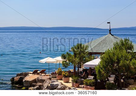 Two Loungers Under Sun Umbrella At The Beach Restaurant In Opatija, Croatia
