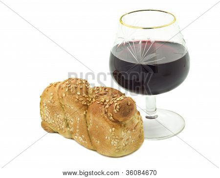 Loaf of  challah  and glass of wine isolated on white background