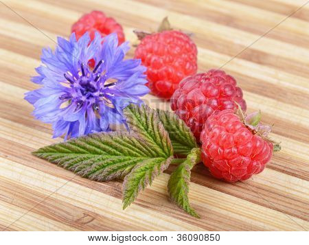 Fresh Ripe Raspberries With Leaf And Blue Flower